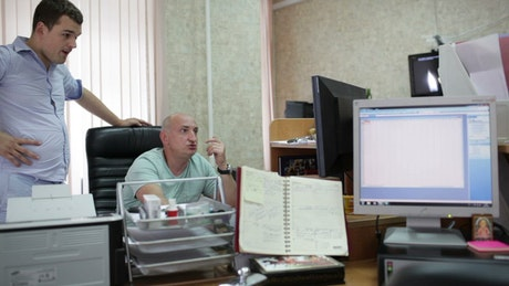 Two men working in a small office