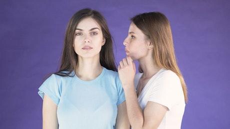 Two models gossip on purple background