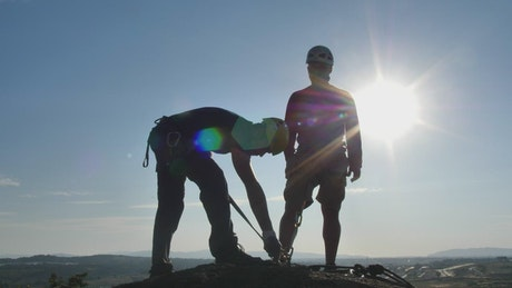Two mountaineers on a peak under the blazing sun