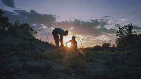 Two mountaineers putting away their things during the sunset