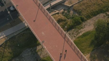 Two people jogging across a footbridge