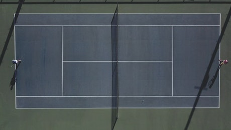 Two people playing tennis aerial view