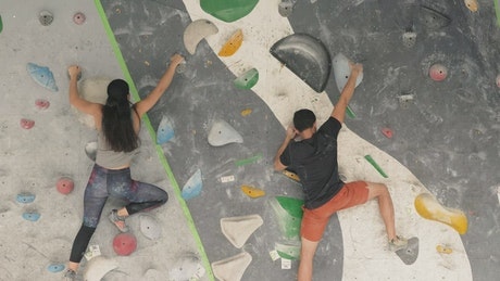 Two people practicing mountaineering on a wall