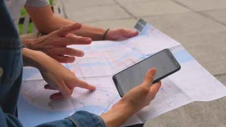 Two people sitting on a bench looking at maps of the area