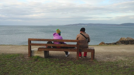Two people sitting on a bench watching the sea