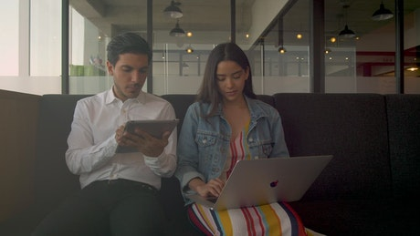 Two people working on electronic devices