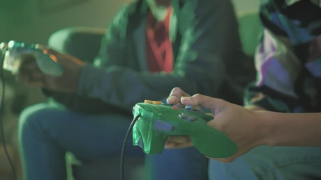 Two players pressing the buttons of a video game control