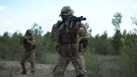 Two soldiers aiming in the battlefield