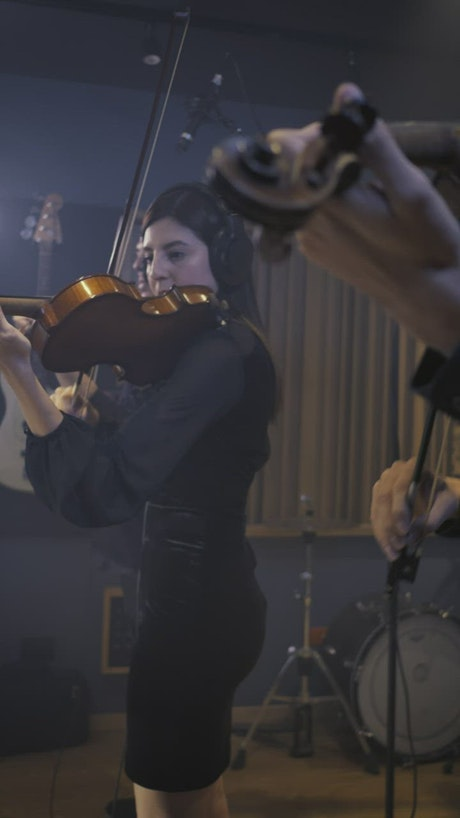 Two talented violinists playing in a recording studio