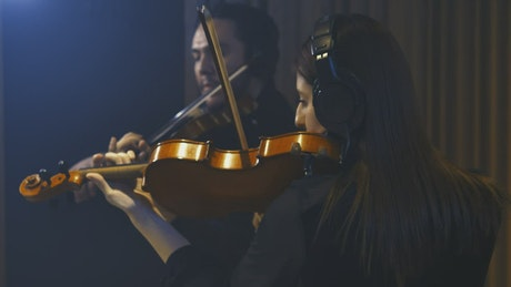 Two talented violinists playing in a studio