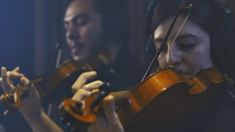 Two violinists playing together recording in a studio