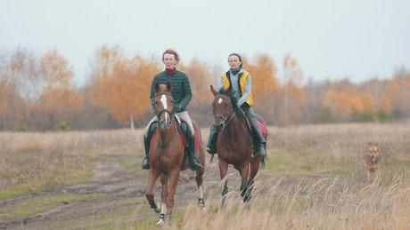 Two women are galloping on the field