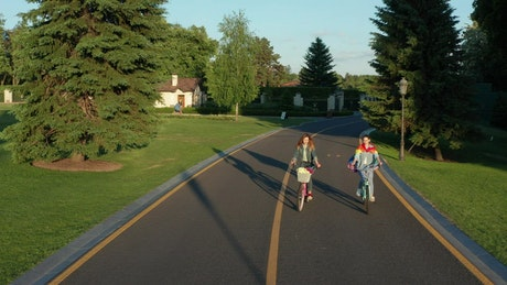 Two women cycling down a road in the suburbs