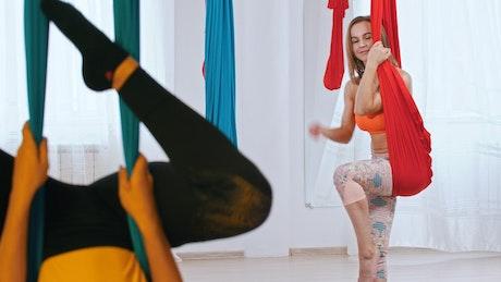 Two women practicing aero yoga in a studio