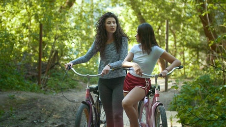 Two women with bicycle crossing through a forest