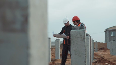 Two workers with blueprint in construction site