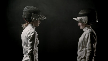 Two young female fencers start fighting