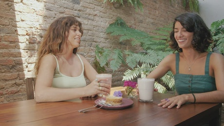 Two young female friends laughing in a coffee shop