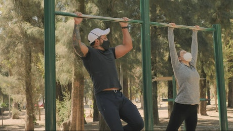 Two young fitness friends doing pull-ups