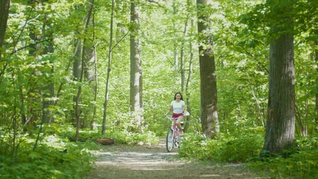 Two young girls riding bicycles in the forest path