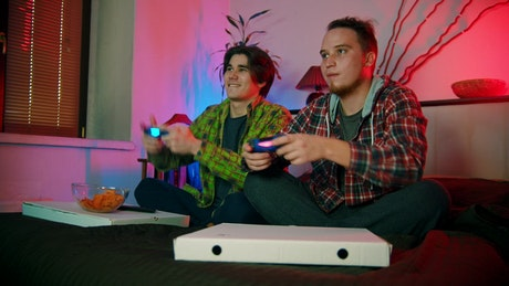 Two young men on the bed playing video games
