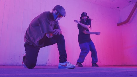 Two young men with face masks dancing hip hop under pink light