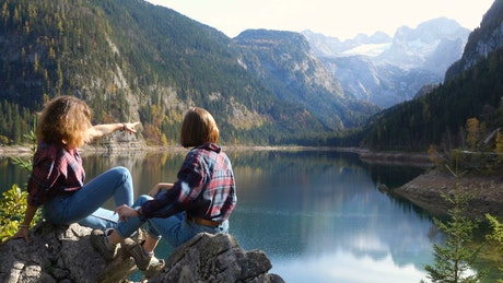 Two young women chilling and watching the lake