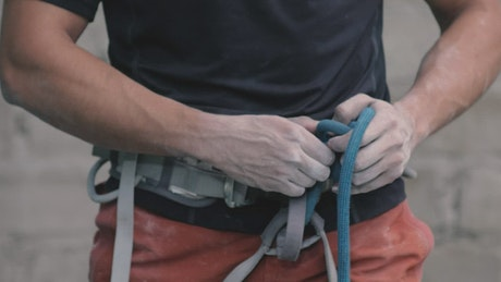 Tying a harness around the waist before mountaineering
