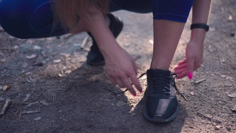 Tying her shoes before jogging