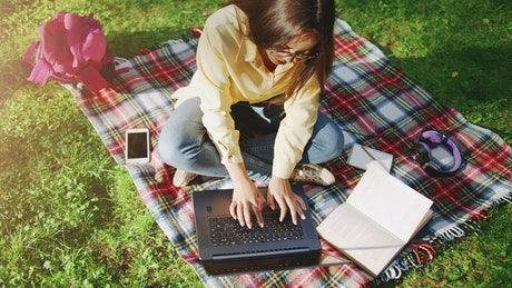 University student learning on laptop in park top view