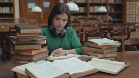 University student researching with books in library