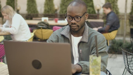 University student smiles at laptop in outdoor cafeteria