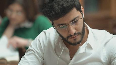 University student studies with earphones in closeup
