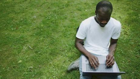 University student types on laptop on green grass