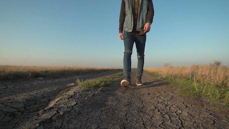 Unknown man walking in a dirt road