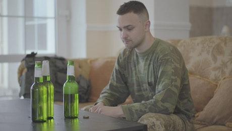 Upset Army veteran sits on sofa drinking beer