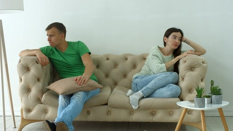 Upset couple sitting in an armchair