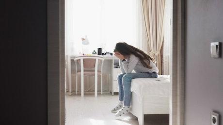 Upset girl sitting on her bed