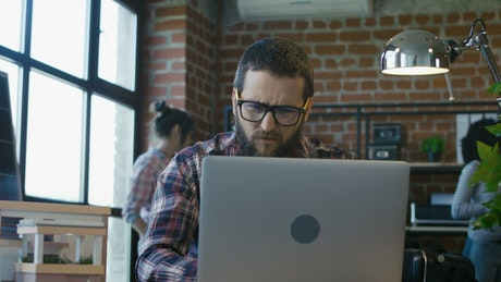 Upset man announcing bad news to coworkers