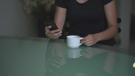 Upset woman checking a cell phone while drinking tea