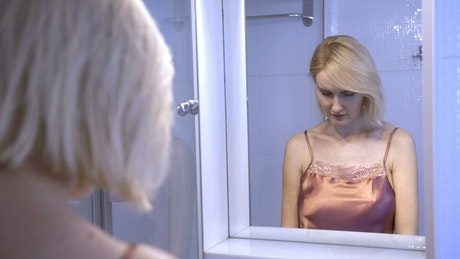 Upset woman looking in the mirror