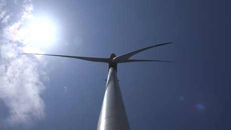 Upward view of a wind turbine with the sky in the background