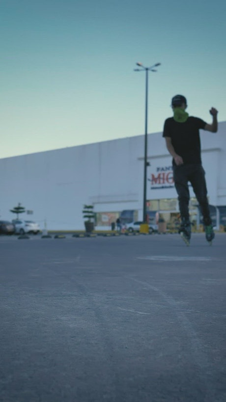 Urban boy with roller skates sliding and spinning in a parking lot