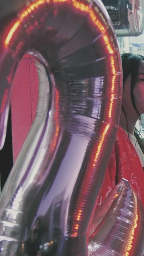Urban girl holding birthday balloons