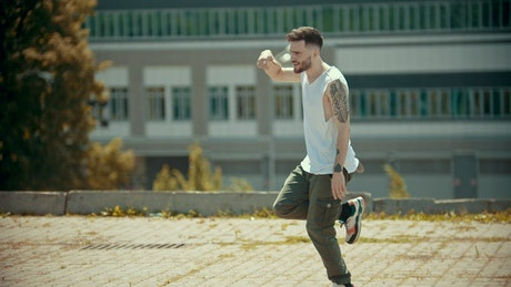 Urban man dancing in the street on a sunny day