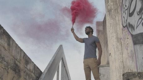 Urban man holding a smoke bomb