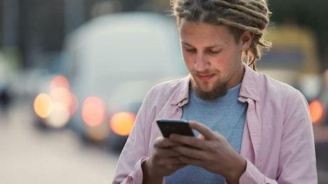 Urban man smiles at social media app in street
