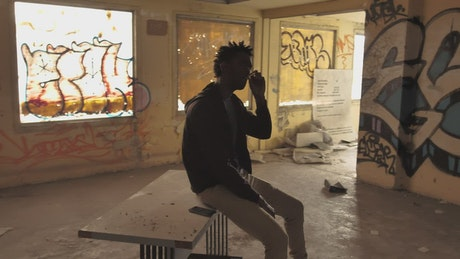 Urban man smoking at a ruined building
