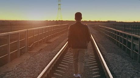 Urban man walking on the train tracks