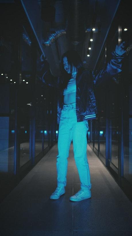 Urban trendy woman dancing in a dark corridor